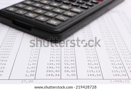 Closeup of financial spreadsheet and calculator lying on sheet in background - stock photo