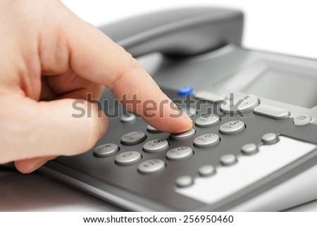 closeup of finger dialing on telephone. customer support concept - stock photo