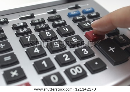Closeup of finger using subtraction key on digital calculator over white background