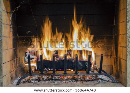 Closeup of firewood burning in fire. Fireplace in the house. Fire in fireplace, firewood burns in a fireplace. Fireplace in a country house. - stock photo