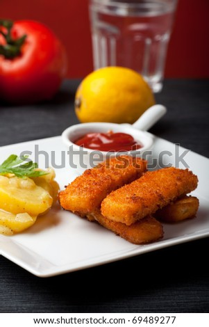closeup of fish fingers with potato salad - stock photo