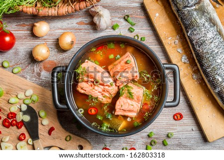 Closeup of fish soup with salmon and dill - stock photo