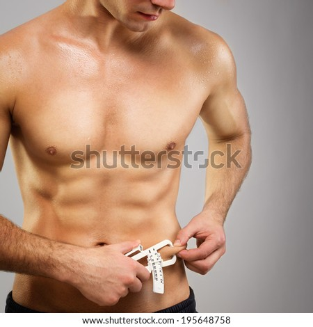 Closeup of fit muscular shirtless Caucasian man with caliper measuring his fat level. Square image, dark gray background, diet, fitness and healthy lifestyle concept. - stock photo