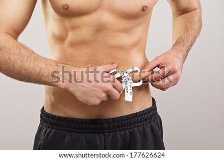 Closeup of fit young sportsman measuring body fat level using caliper. Diet, fitness, healthy lifestyle and body care concept. - stock photo