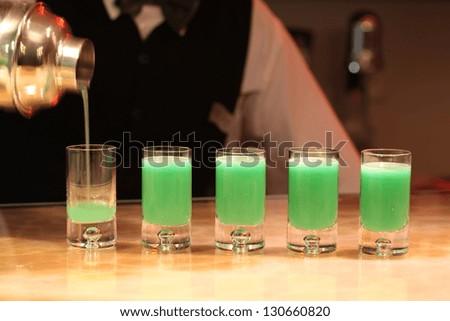 Closeup of five green absinthe alcohol shots - stock photo