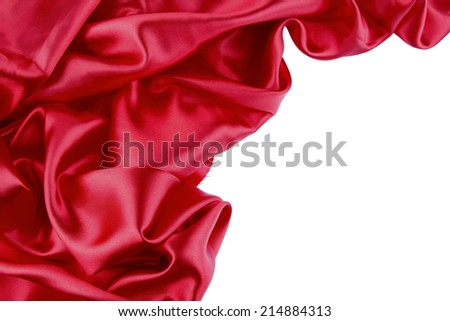 Closeup of folds in red silk fabric on plain background. Copy space