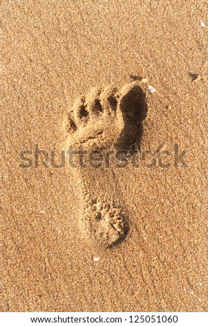 Closeup of foot print on sand beach - stock photo