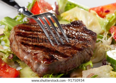 closeup of fork on a grilled steak - stock photo