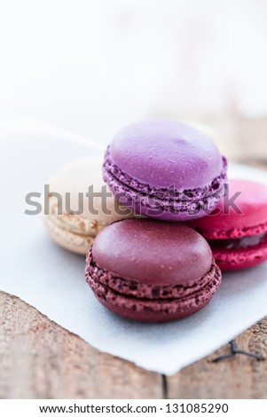 Closeup of four different flavored macaroons on wooden table - stock photo