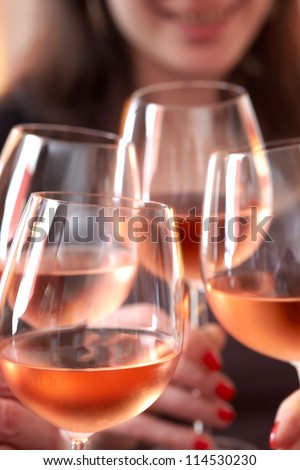 Closeup of four glasses with wine being clinked together during a toast at a celebration - stock photo