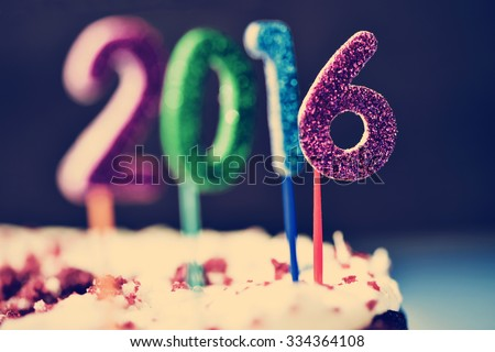 closeup of four glittering numbers of different colors forming the number 2016, as the new year, topping a cake - stock photo