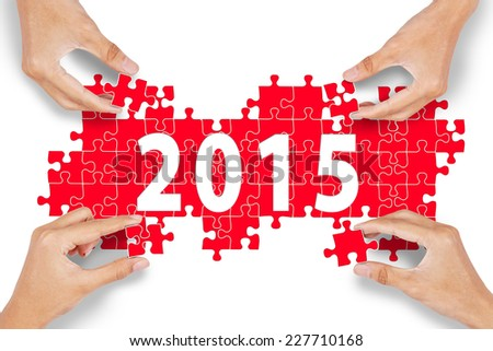 Closeup of four hands arrange number 2015 to celebrate new year of 2015 - stock photo