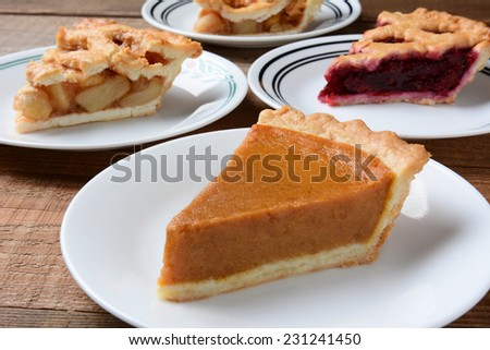 Closeup of four slices of pie on dessert plates. Focus is on the front slice of pumpkin pie. The back plates have apple and cherry pie. Horizontal format on an old wood kitchen table. - stock photo