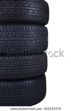 Closeup of four tires with black color stacked in the studio, isolated on white background - stock photo