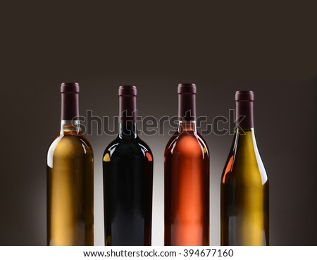 Closeup of four wine bottles with no labels on a light to dark gray background.  - stock photo