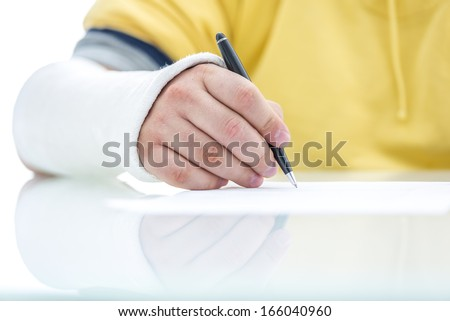 Closeup of fractured male hand in plaster signing insurance claim. - stock photo