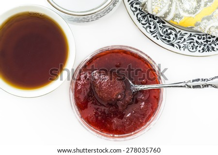 Closeup of fresh cooked strawberry jam and cup of tea.