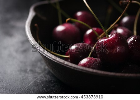 Closeup of fresh red cherry on an old pan with copy space, horizontal - stock photo