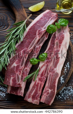 Closeup of fresh uncooked seasoned beef ribs, selective focus