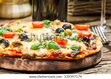 Closeup of freshly baked pizza served with wine