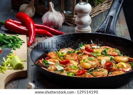 Closeup of freshly fried shrimps with herbs - stock photo