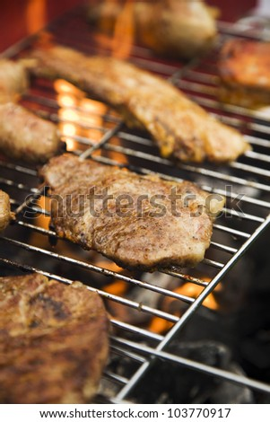 Closeup of fried burgers and meat on grill in fire background