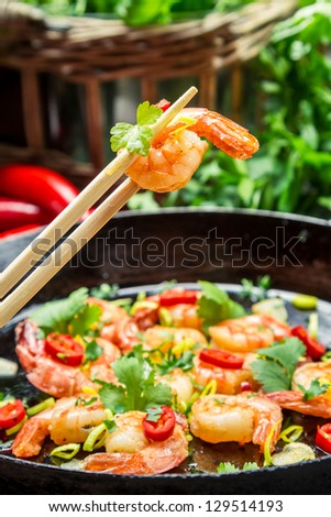 Closeup of fried shrimp on chopsticks with herbs