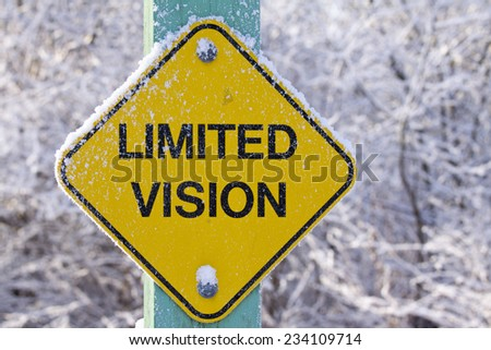 Closeup of frozen sign warning of limited vision ahead