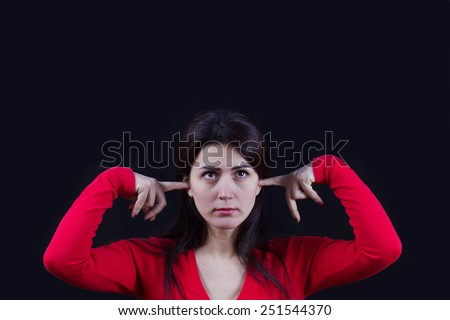 Closeup of frustrated,bored young woman holding her ears, closing ears isolated on black background. - stock photo