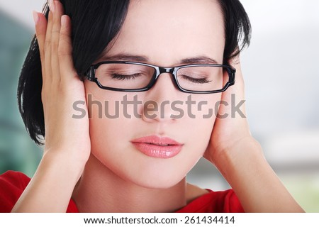 Closeup of frustrated young woman holding her ears - stock photo