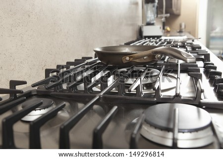 Closeup of frying pan on stove in commercial kitchen - stock photo