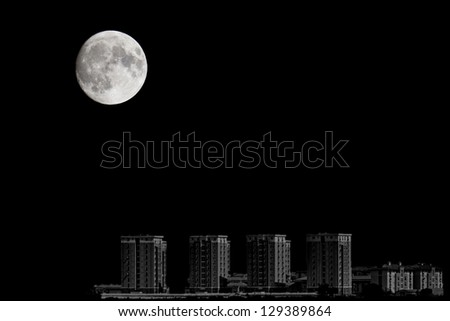 Closeup of full moon over the city - stock photo