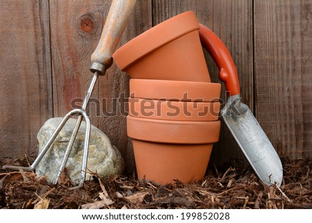 Closeup of garden tools and flower pots against a wooden backyard fence. - stock photo
