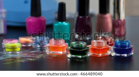 Closeup of gel polishes and powder for nails on the table