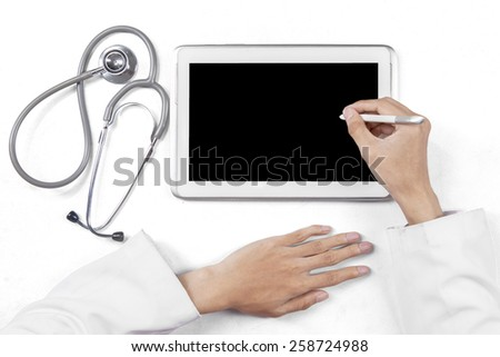 Closeup of general doctor hands using stylus pen to touch the digital tablet screen - stock photo