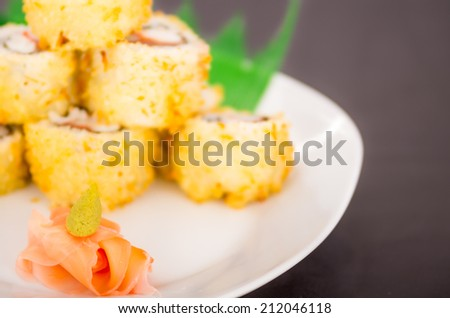 Closeup of ginger and wasabi decoration and sushi rolls in the background selective focus - stock photo