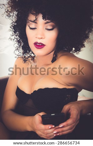 closeup of girl in lingerie sitting on sofa playing with phone