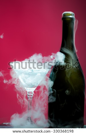 Closeup of glamour open full champage wive sweet or dry drink green glass bottle and goblet with beautiful white smoke for celebration christmas or new year on pink background, vertical picture - stock photo