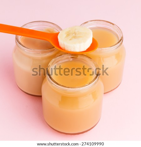 Closeup of glass jars of baby food with banana slice on plastic spoon on pink background  - stock photo