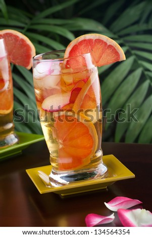 Closeup of glass of grapefruit and rose iced tea on a table in a restaurant on a tropical beach.