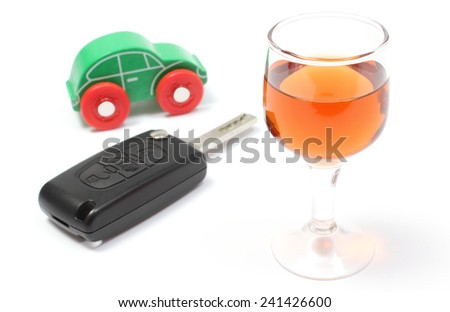 Closeup of glass of wine with car key and old wooden toy car, key car and alcohol, don't drink and drive concept. Isolated on white background - stock photo