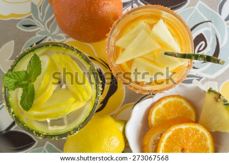 Closeup of glasses of tangerine, pineapple and lemon, mint infused water.