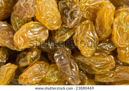 Closeup of gold colored raisins and wooden spoon - stock photo