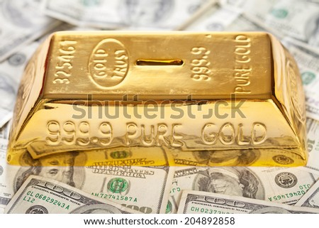 Closeup of golden bullion like moneybox on hundred dollars banknotes background - stock photo