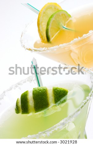 Closeup of Golden Margarita and Midori Margarita tequila cocktails garnished with lime and lemon wedges - stock photo