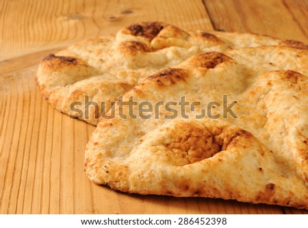 Closeup of golden naan bread on a rustic wooden table - stock photo