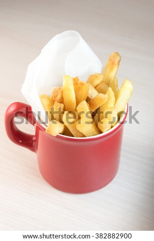 Closeup of golden tasteful yummy chips in red ceramic cup - stock photo