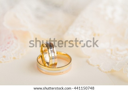 Closeup of golden wedding rings on pastel lace background. Shallow focus