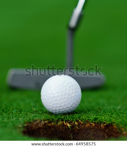 Closeup of golf ball, cup and putter on the green