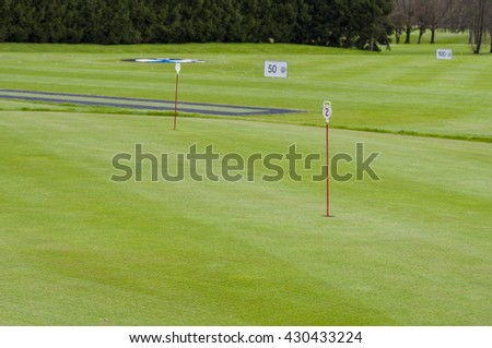 Closeup of golf green with hole and flag on golf course - stock photo